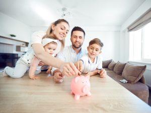 family putting money into a piggy jar