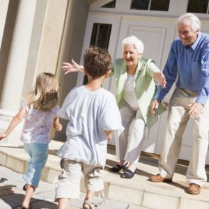 grandparents greeting their grandkids at their home in retirement