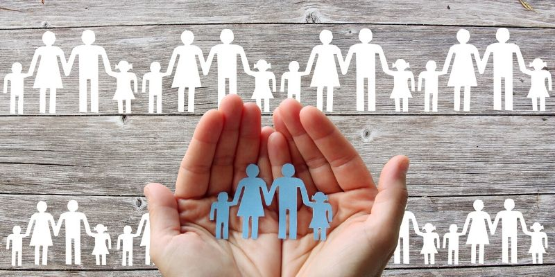 Family dimension of wealth - graphic of hands holding paper cutout of family members