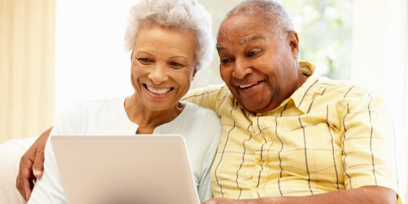 Couple smiling at laptop