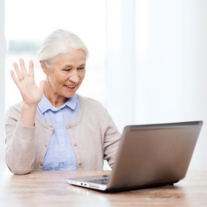 Woman on video call waving to laptop